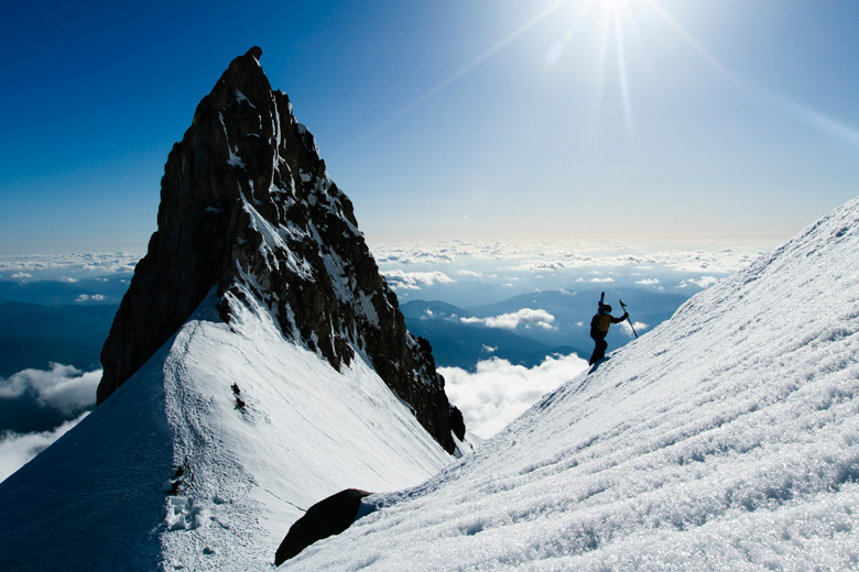 Skier Ascending Mountain | Why & How To Carry Water While Skiing: Hydration Tips for Skiers